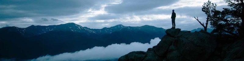 Man Climbing Dark Mountain
