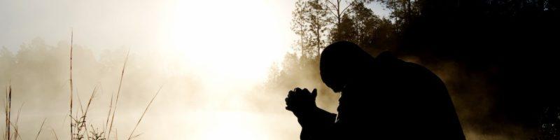 Man Praying in Field